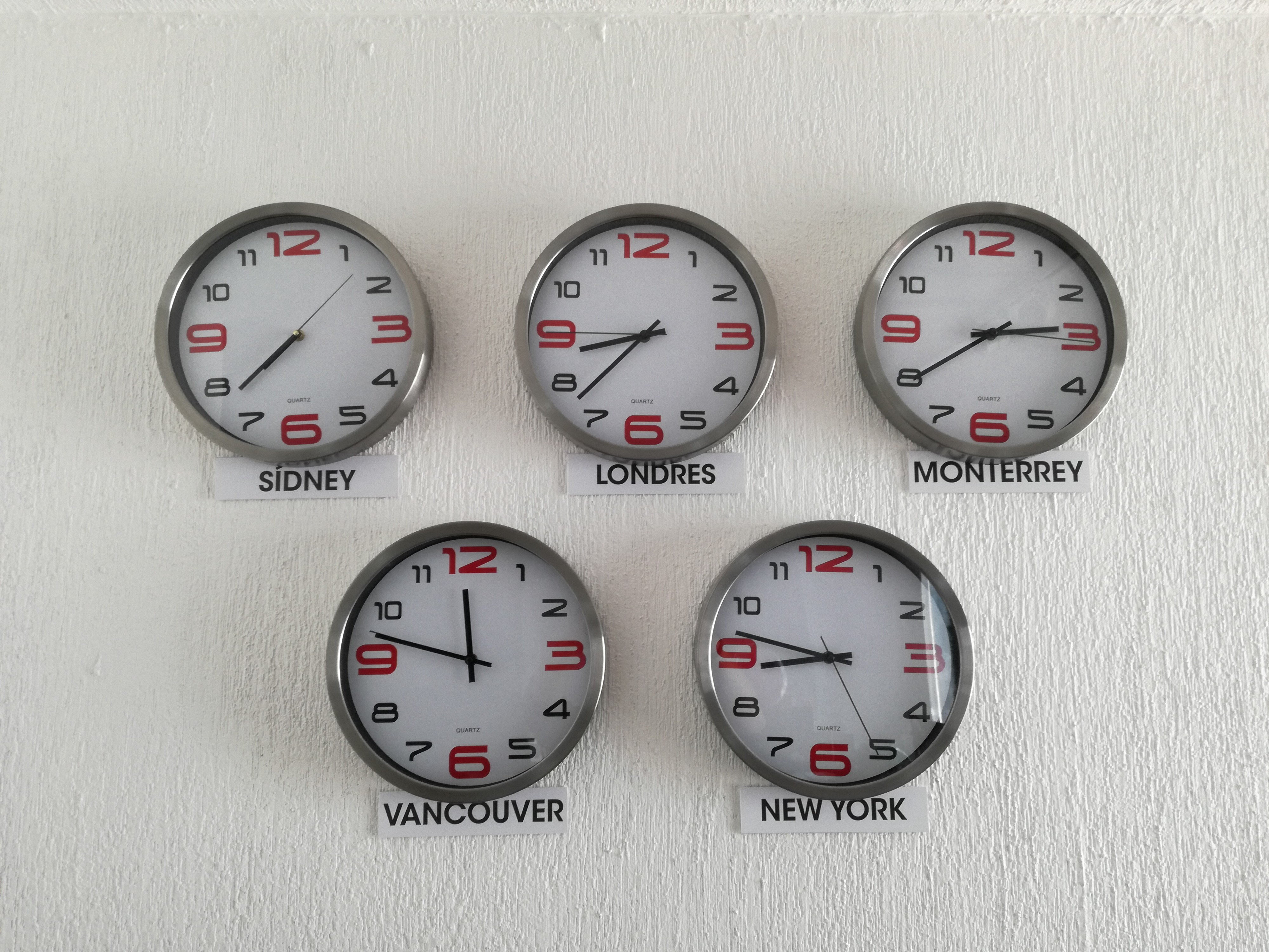 Five clocks hanging on a wall, pointing at different time zones.