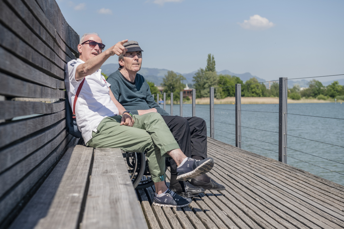 Ein Betreuer des Entlastungsdienstes Schweiz begleitet einen erwachsenen Mann mit körperlicher Behinderung auf einem kleinen Ausflug. Damit entlastet er auch betreuende Angehörige.
