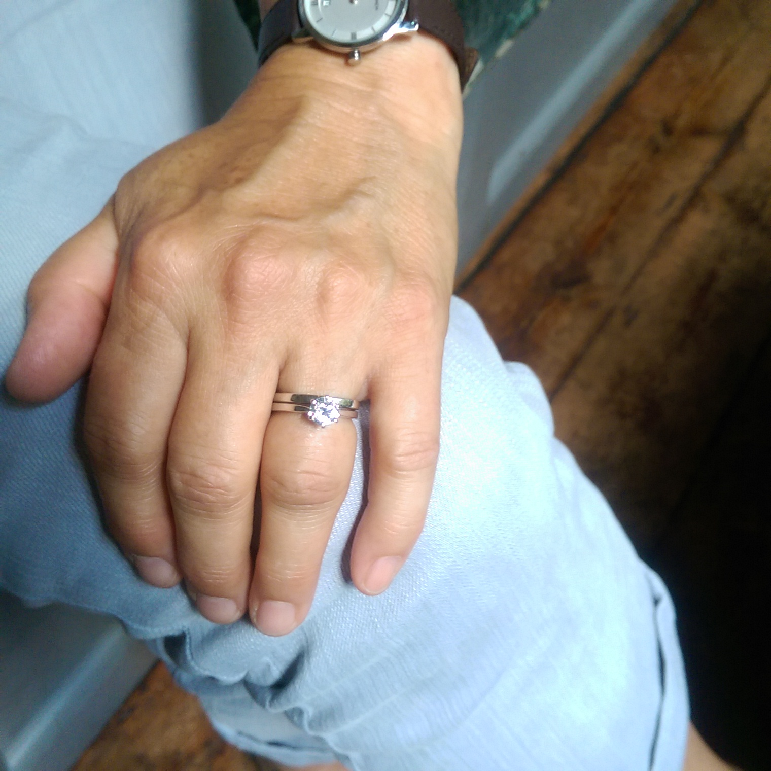Finished trapezoid shaped engagement wedding and engagement ring on client hand.