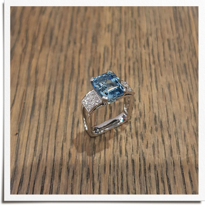 Finished art deco inspired ring with emerald shape aquamarine centre stone and round side diamonds either side in three rows and square frame. Square ring shank stops spin.