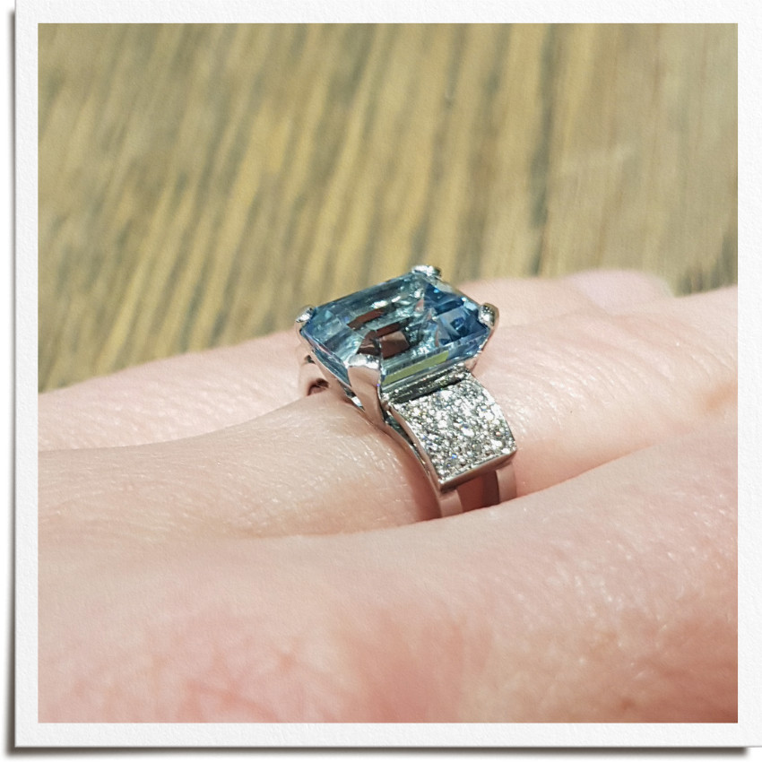 Finished art deco inspired ring on hand from side with emerald shape aquamarine centre stone and round side diamonds either side in three rows and square frame. Square ring shank stops spin.