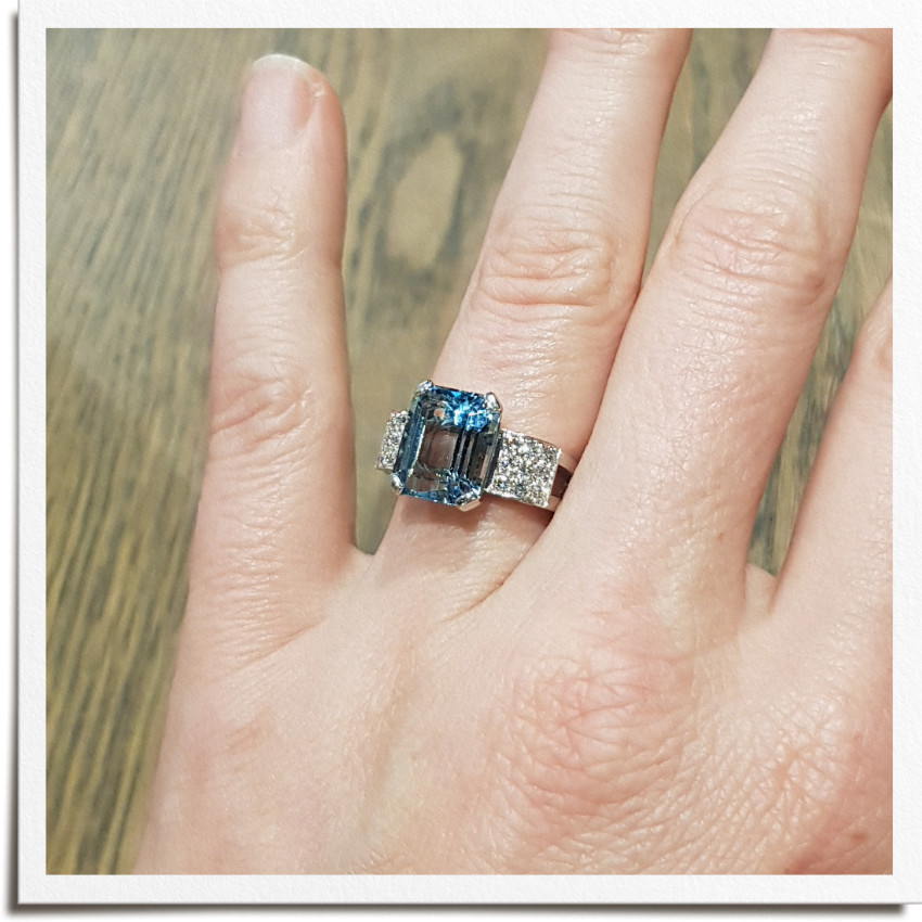 Finished art deco inspired ring on hand from top with emerald shape aquamarine centre stone and round side diamonds either side in three rows and square frame. Square ring shank stops spin.