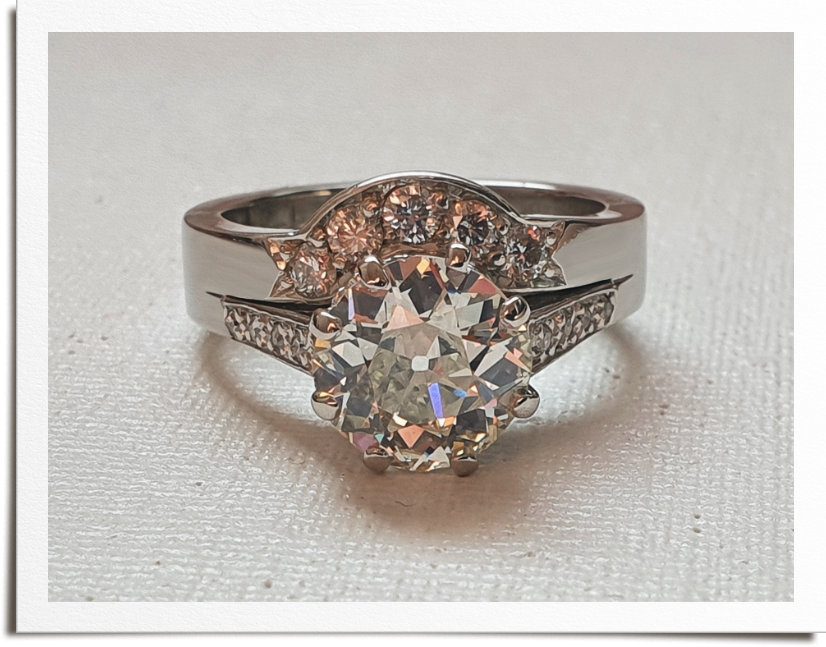 Front view of finished wedding and engagement ring with large round diamond and wedding band shaped around stone setting.