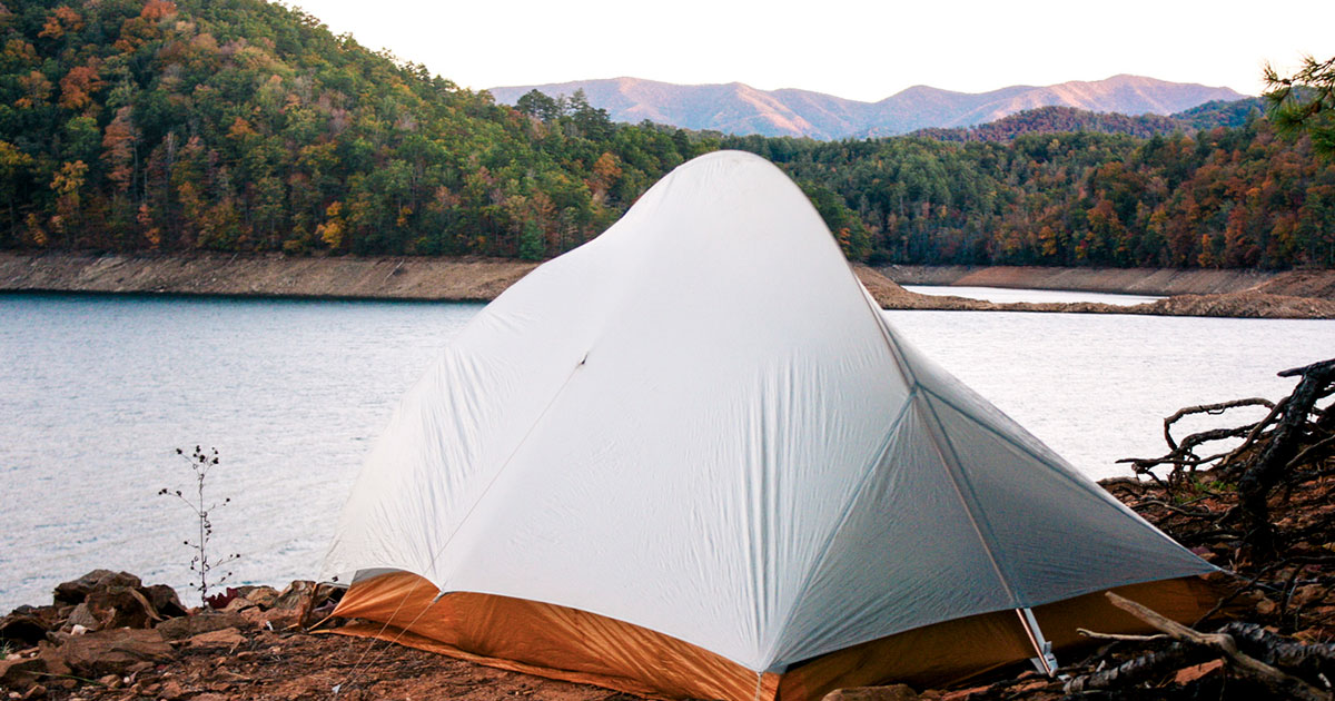 Camping tent in front of lake.