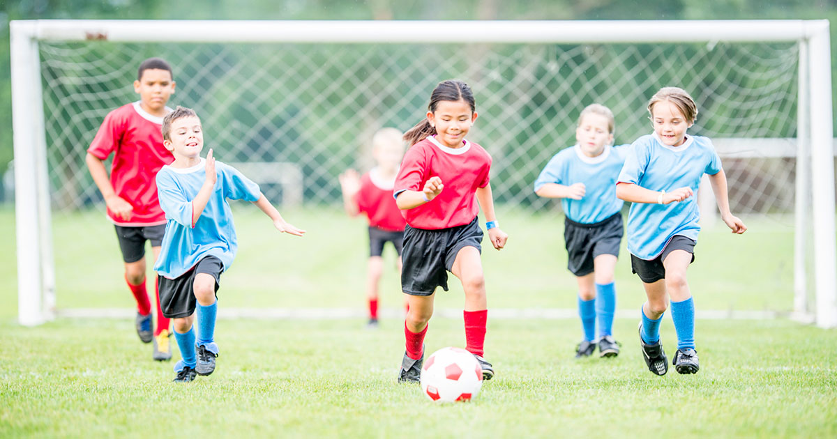 Children in red and blue soccer jerseys running after a soccer ball.