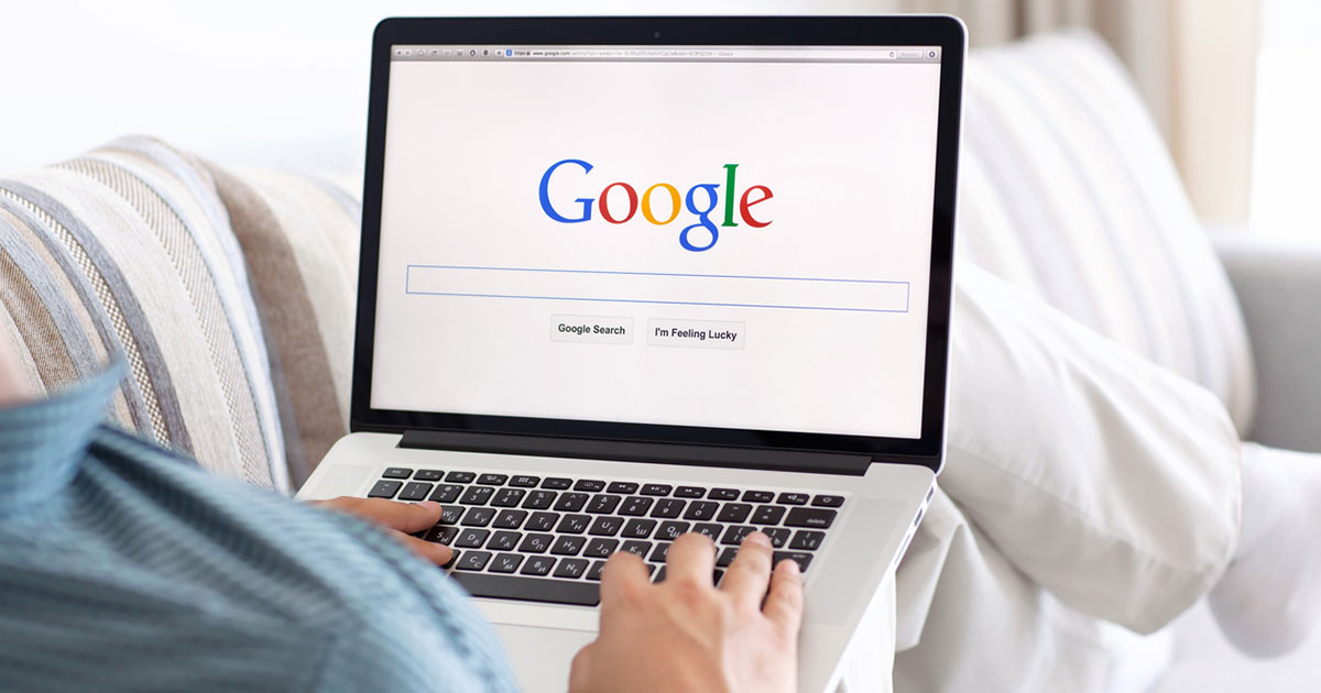 Person looking at the Google search page on their laptop.