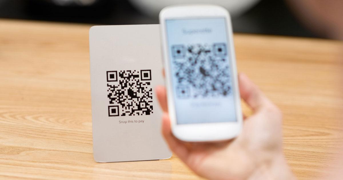 A person scanning a QR code via their smartphone.