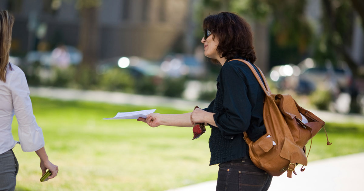 Woman with brown backpack passing out a flyer.