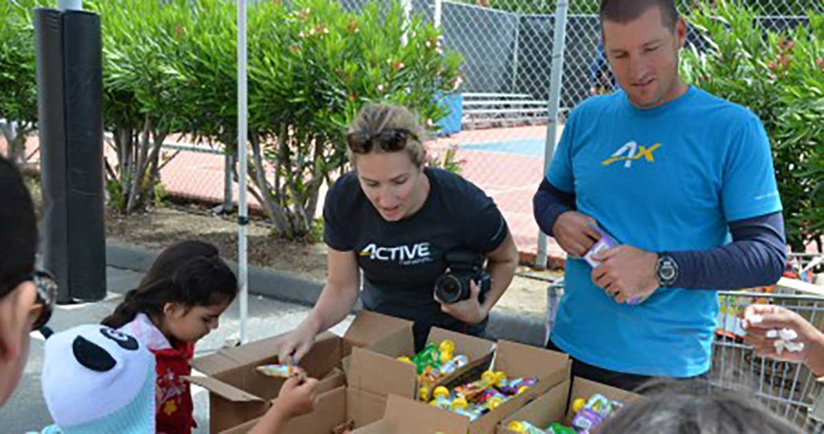 Employees volunteering and helping out kids.