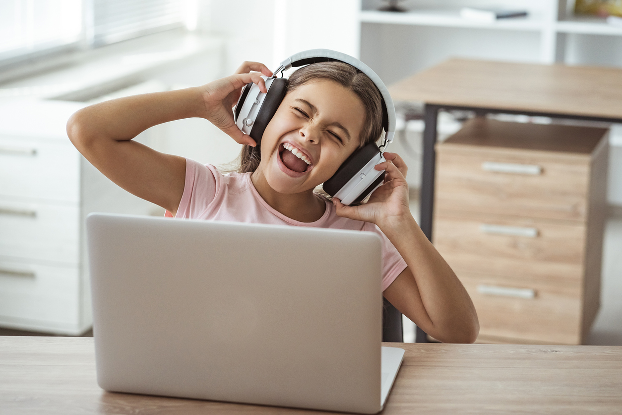 young girl listening to music on her laptop with headphones