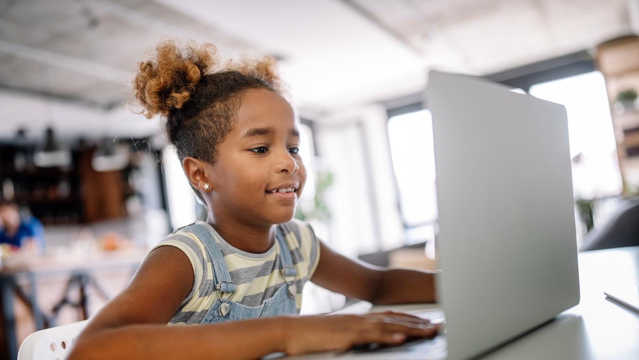 Little girl on laptop smiling. White chair at desk.