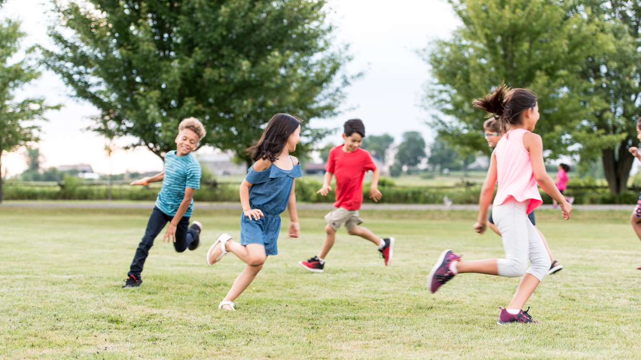 Kids running in circles playing games outdoors.