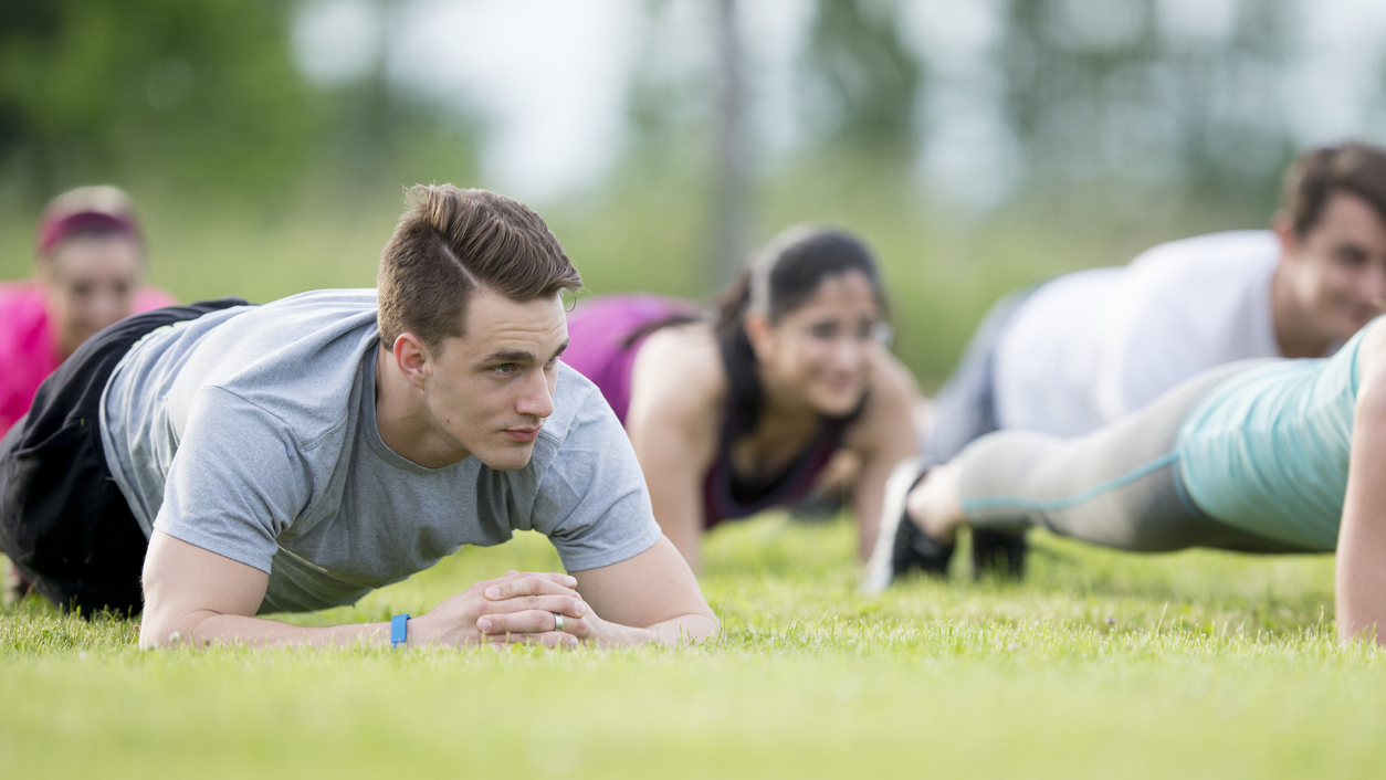 Group of people working out, holding the plank position at an outdoor bootcamp class.
