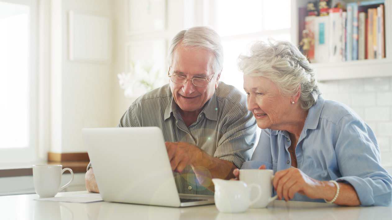 Older man and woman sitting at a table on a white laptop smiling.