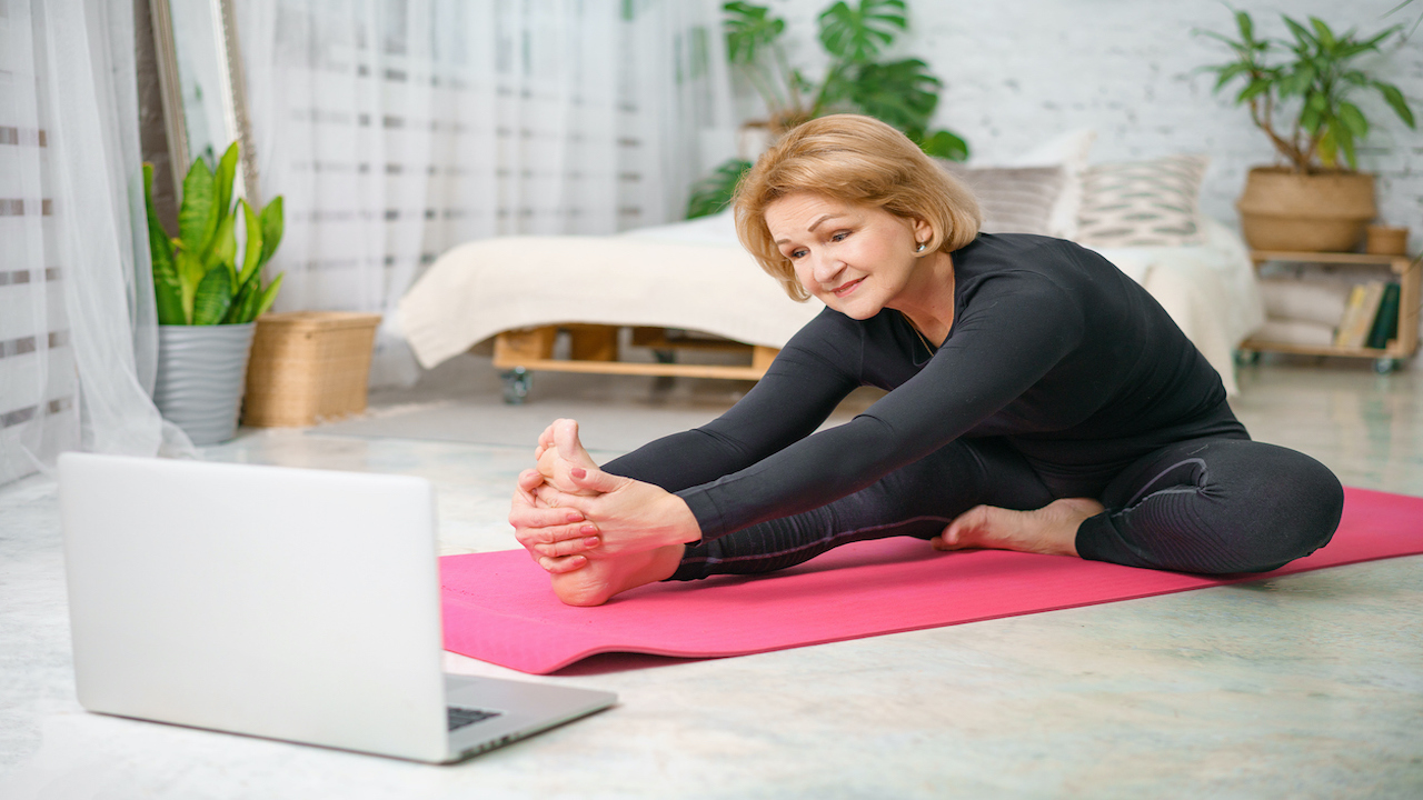 Senior citizen practicing yoga in front of computer with pink yoga mat.