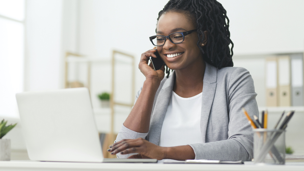 Professional on computer and phone in an office.