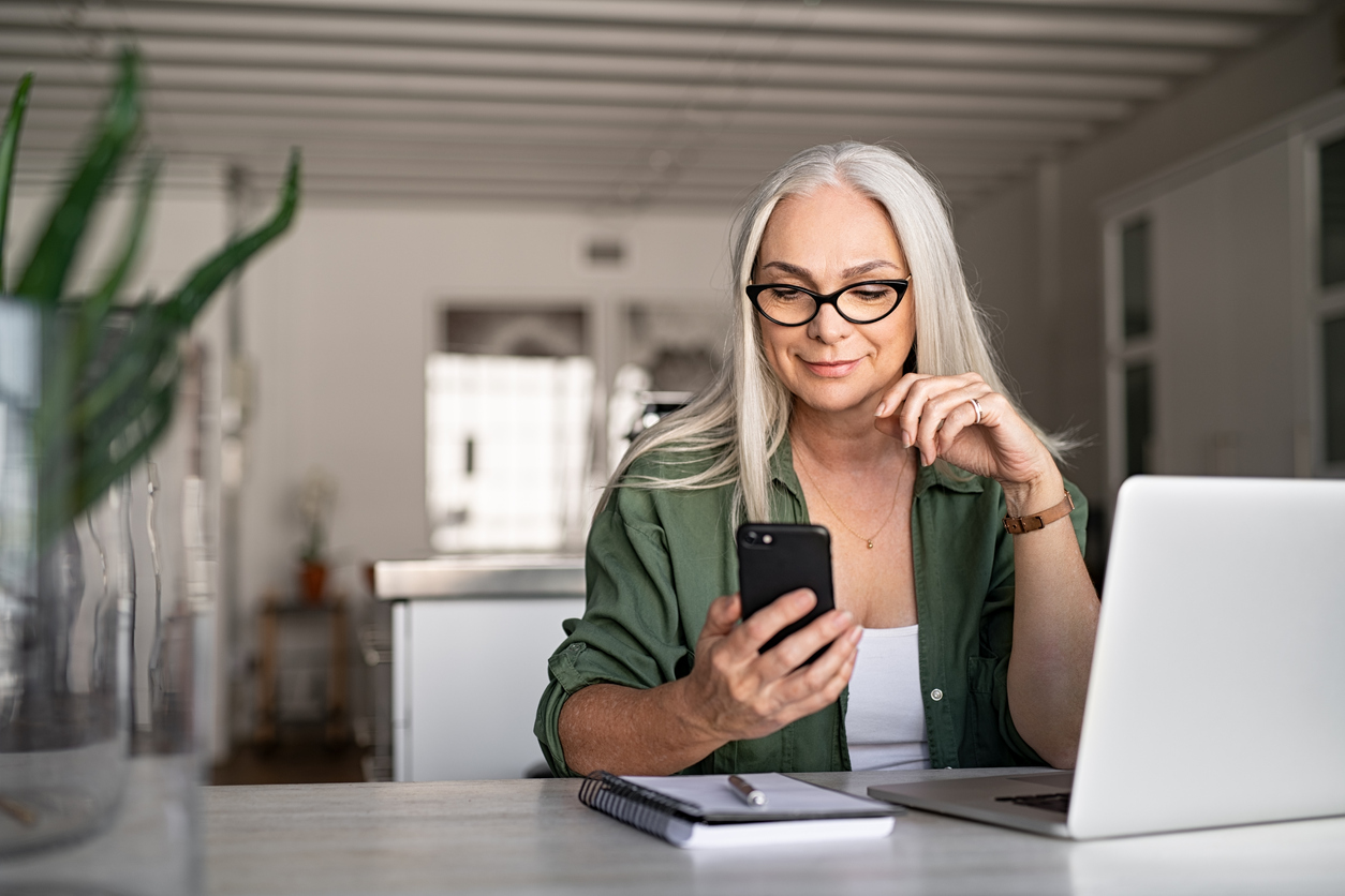 Silver haired woman on smartphone and using computer at a desk.