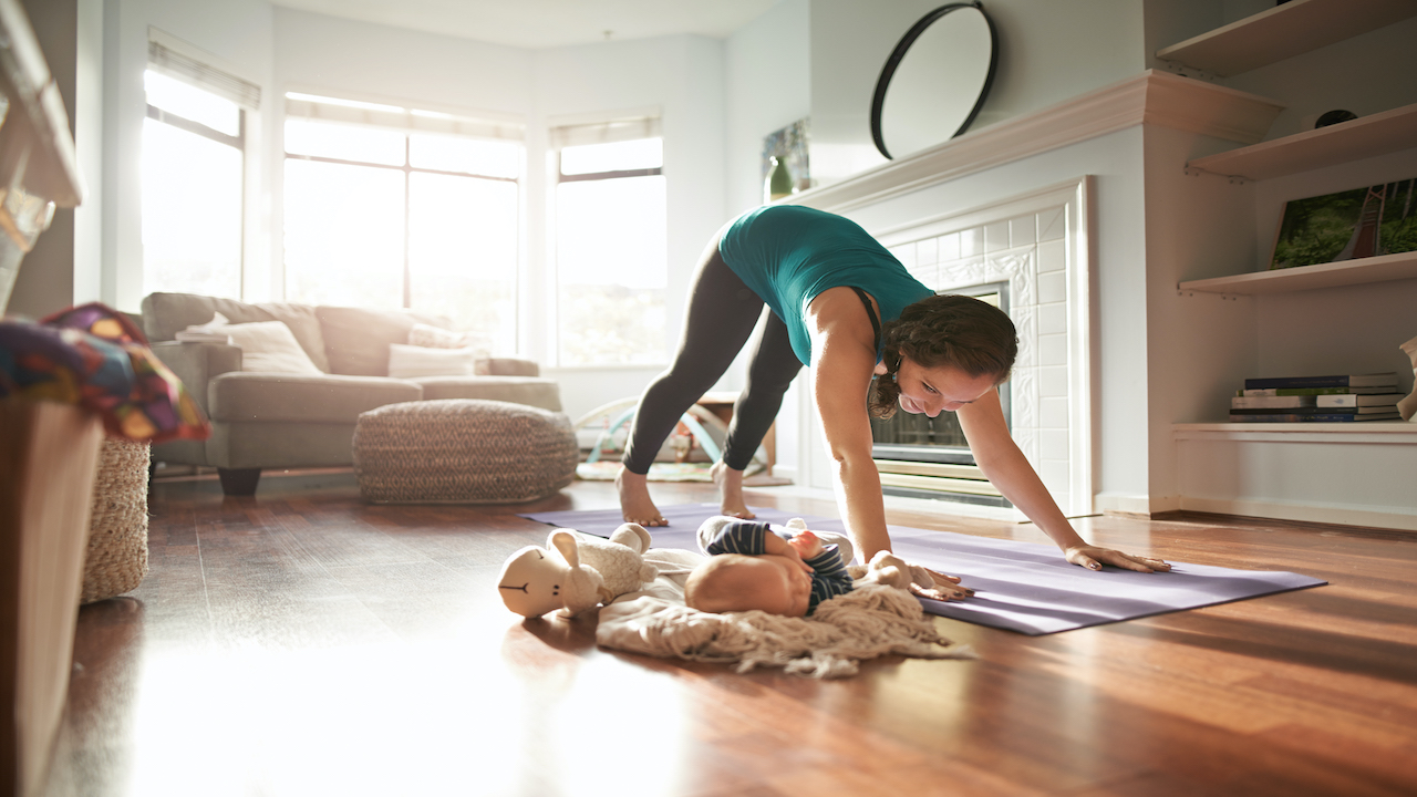 Mother in downward dog yoga pose in living room with baby by her side.