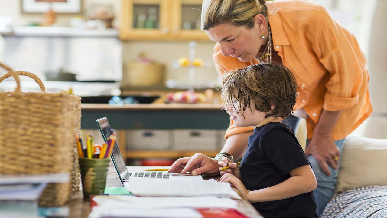 Woman in orange top helping kid on a computer with school work.