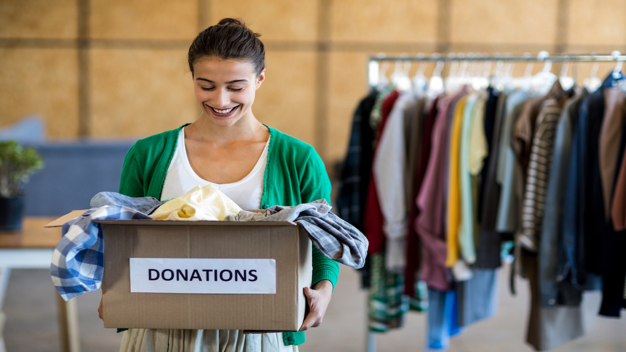 Woman holding a box of clothing donations with rack of clothing behind her.