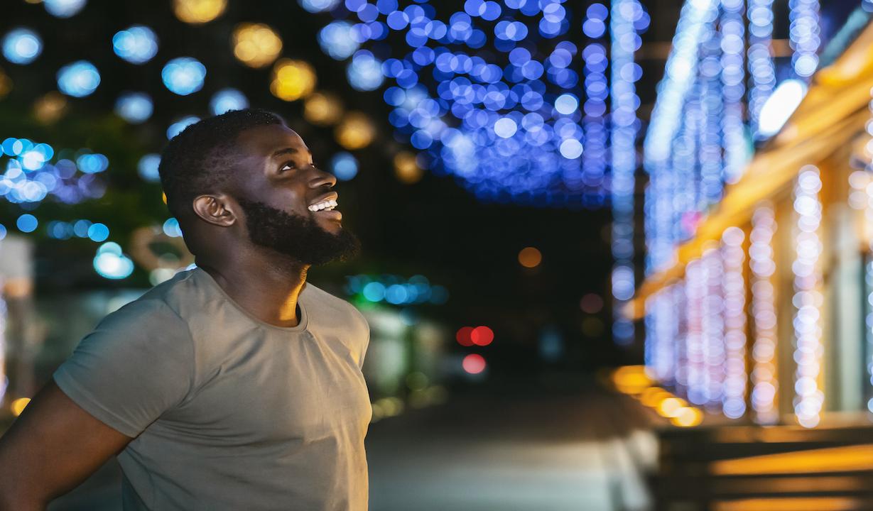 Man outside at night looking at Christmas lights.