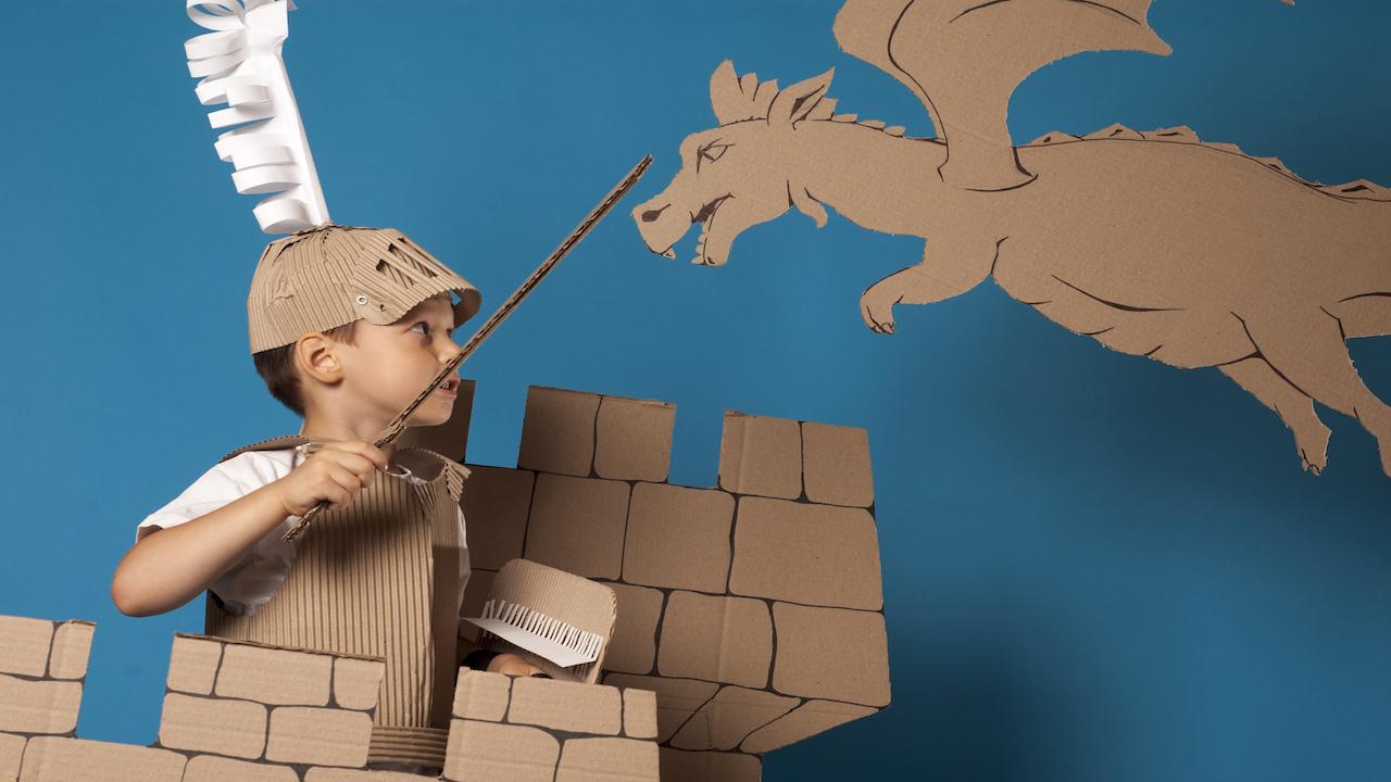 Child in cardboard castle fighting cardboard dragon