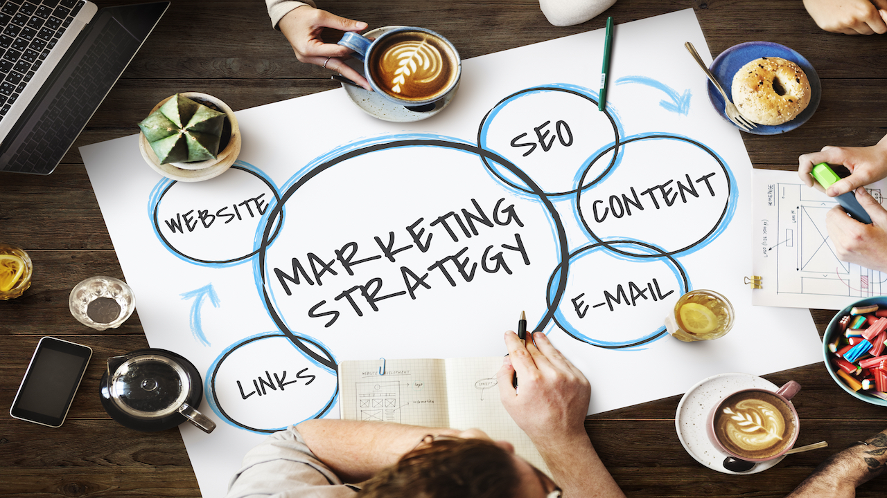 Overhead view of marketing strategy with hands all around on a table.