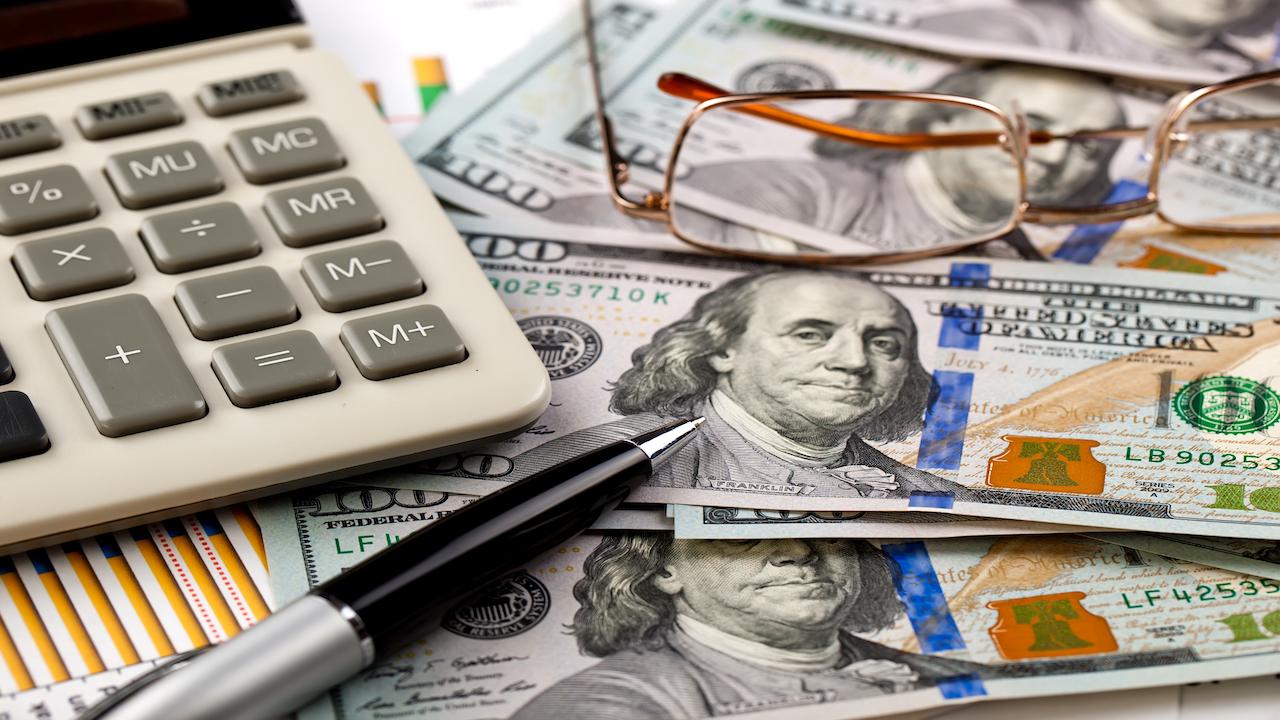 Calculator, pen, $100 bills scattered across a desk