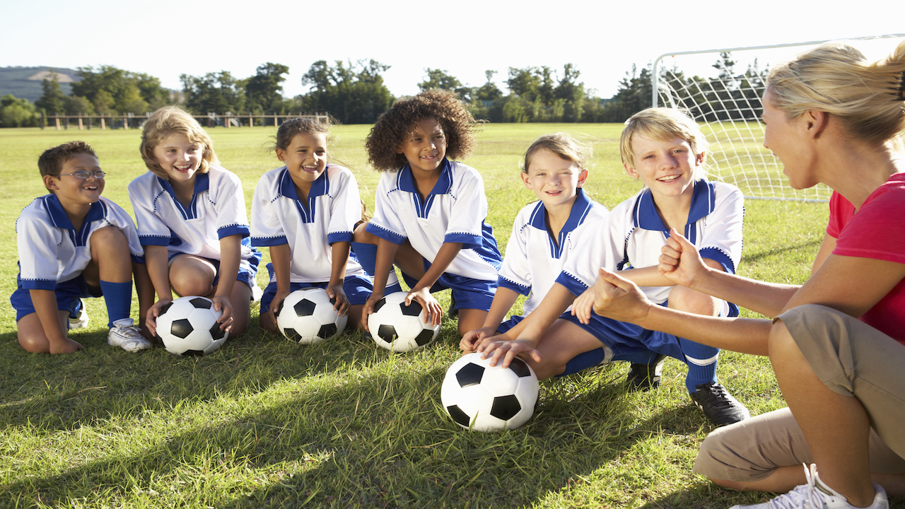 Kids soccer team with female coach.