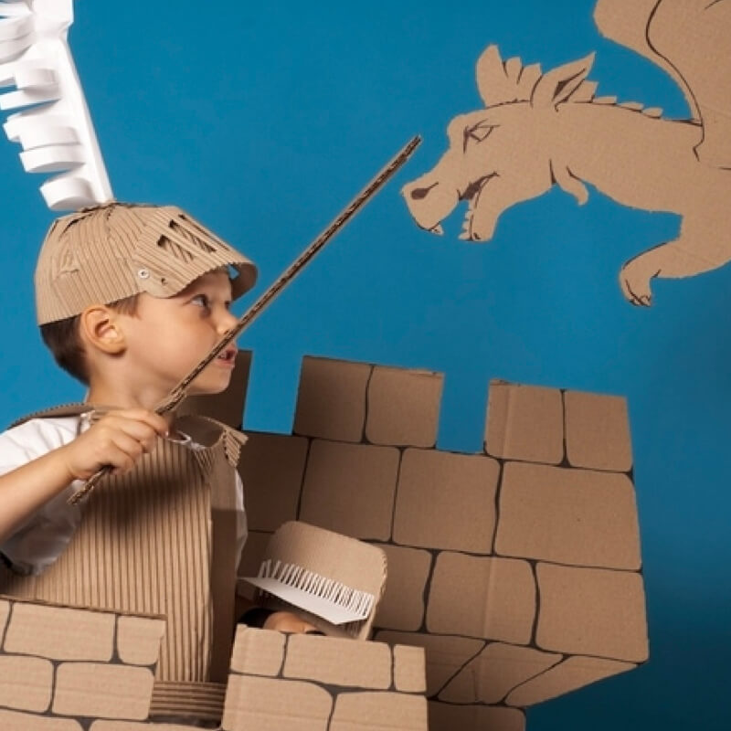 child slaying a dragon playing in cardboard outfit