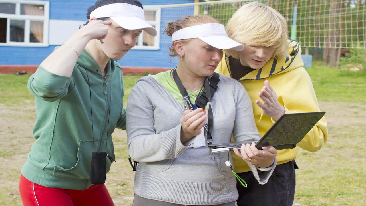 Three camp counselors looking at a computer.