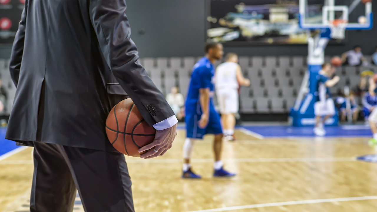 College basketball coach holding basketball watching players on the court.