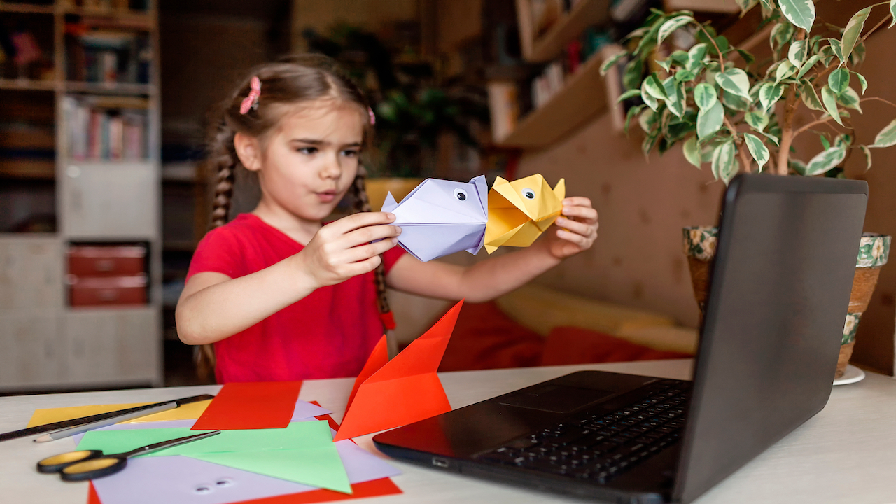 Little girl in red dress and pig tails making fish origami with computer.