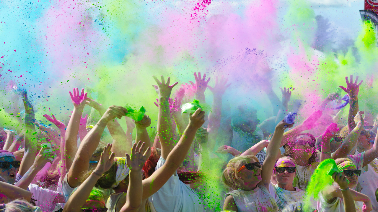 People throwing powdered color in the air during a fun run event.