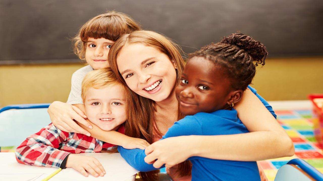 Child care teacher hugging three kids.