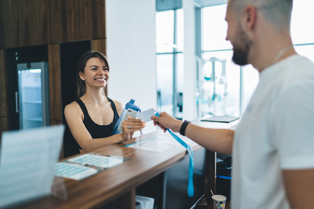 Woman smiling at the front desk attendant as she checks in to the local rec center.