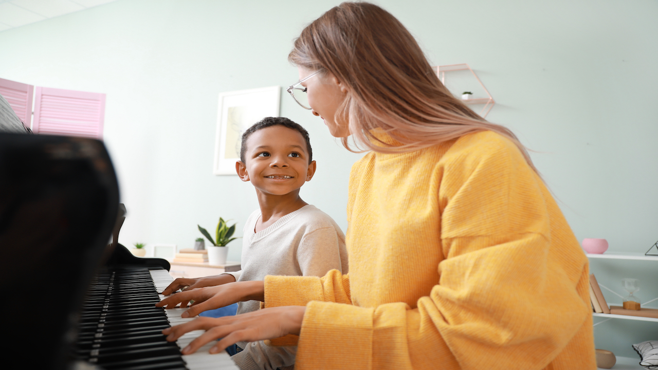 Teacher in a yellow shirt at a piano with smiling student.
