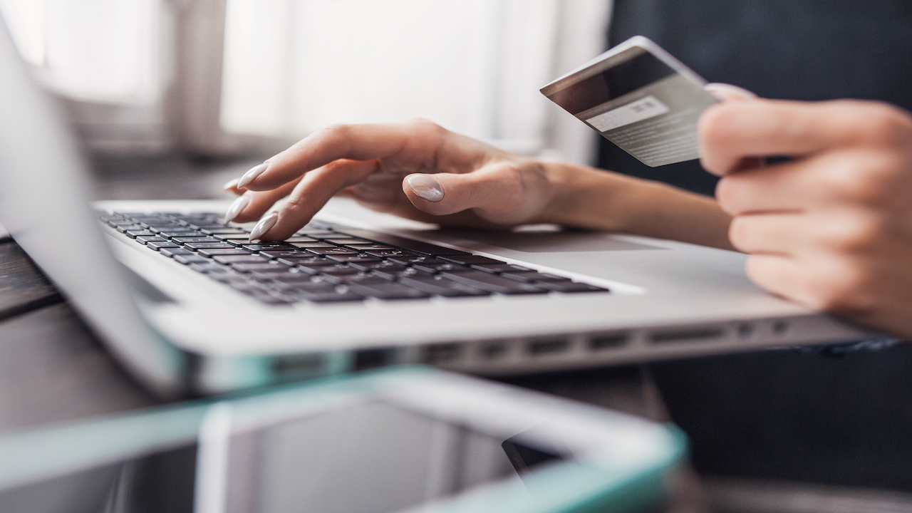 Hands holding a credit card attempting to make a purchase on a computer.