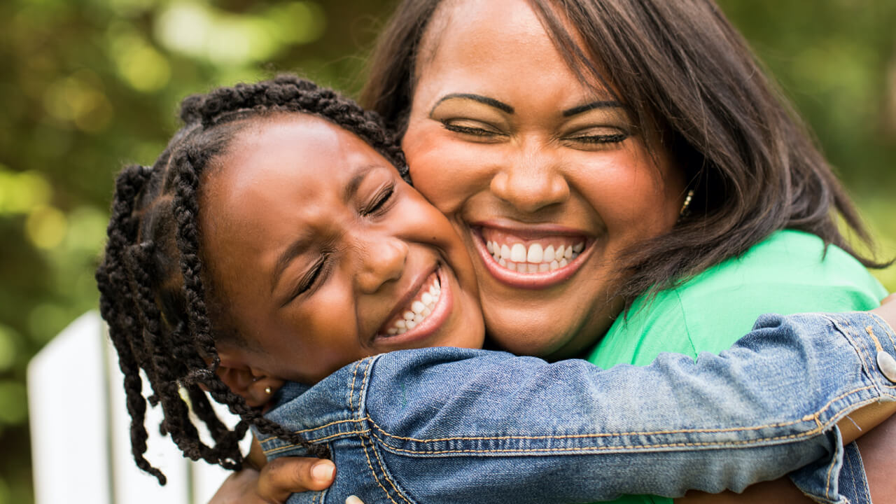 Mother and daughter hugging each other and smiling outside.