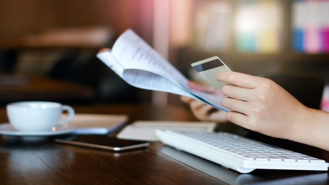 Person looking at bank statement while holding a credit card.