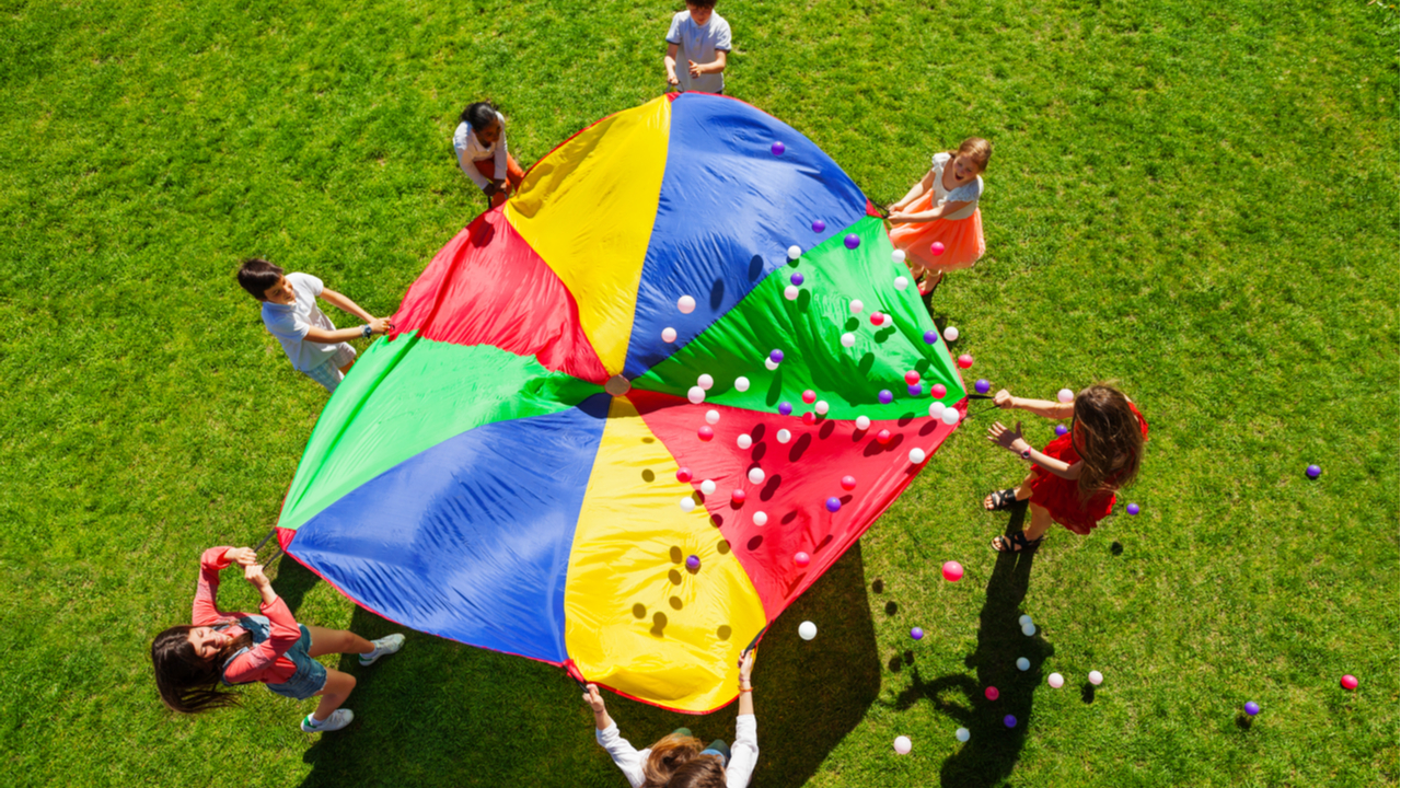 Overhead shot of children playing with a multi-colored parachute.