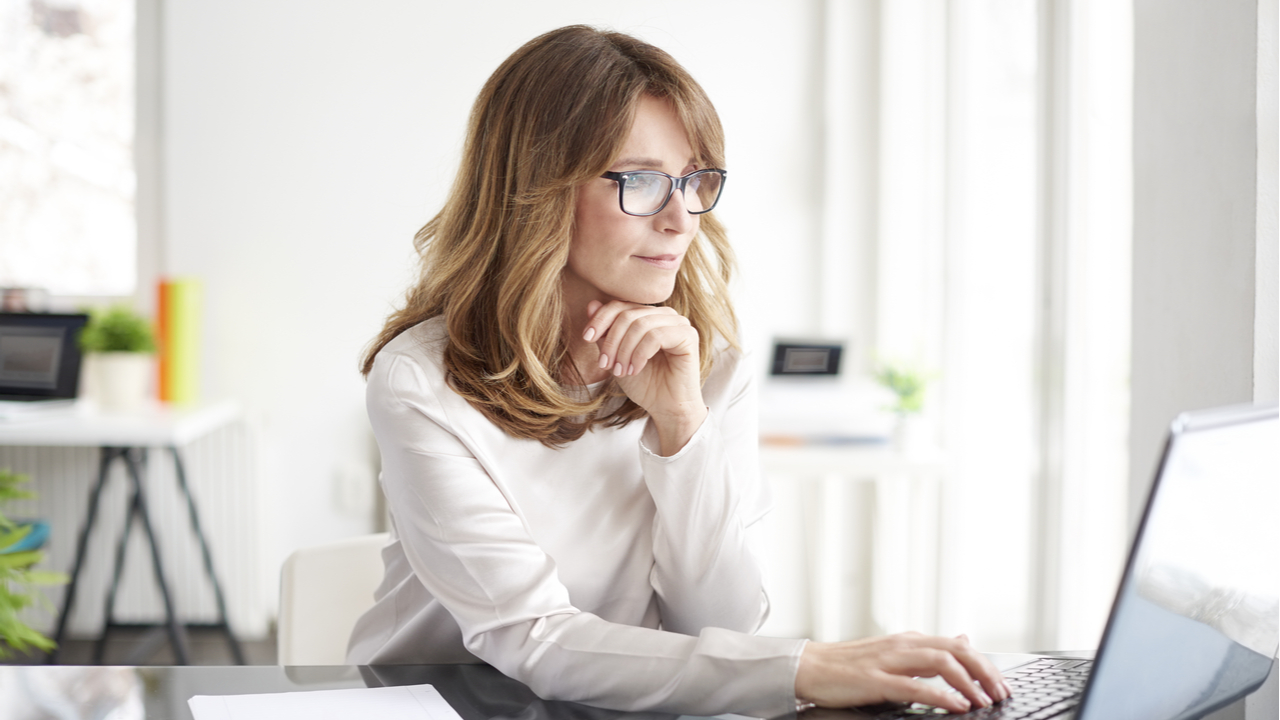 Woman with blond hair and glasses looking at her computer at a desk.