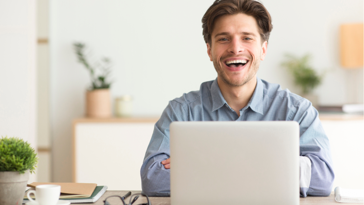 Man sitting and smiling at a desk with a laptop in front of him.