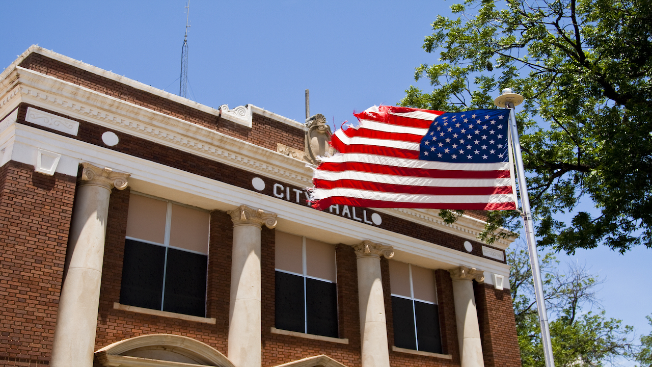 City Hall building with American flag.
