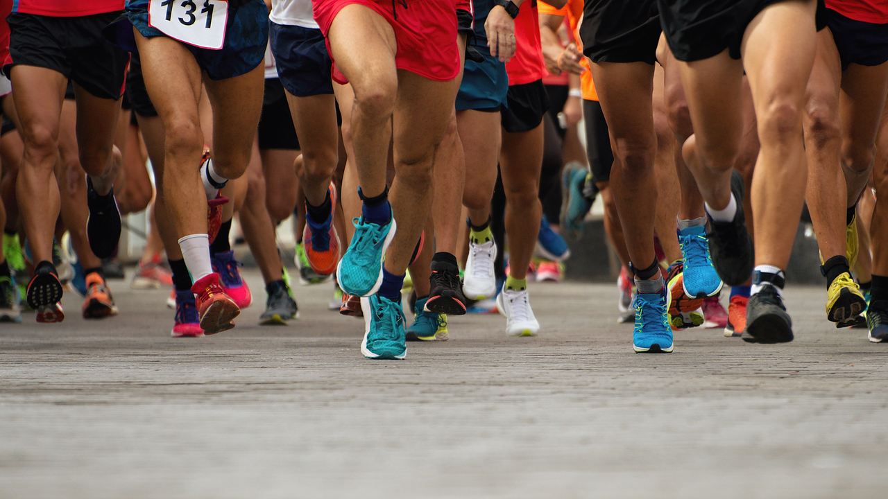 Shot of peoples legs and feet as they run a marathon.