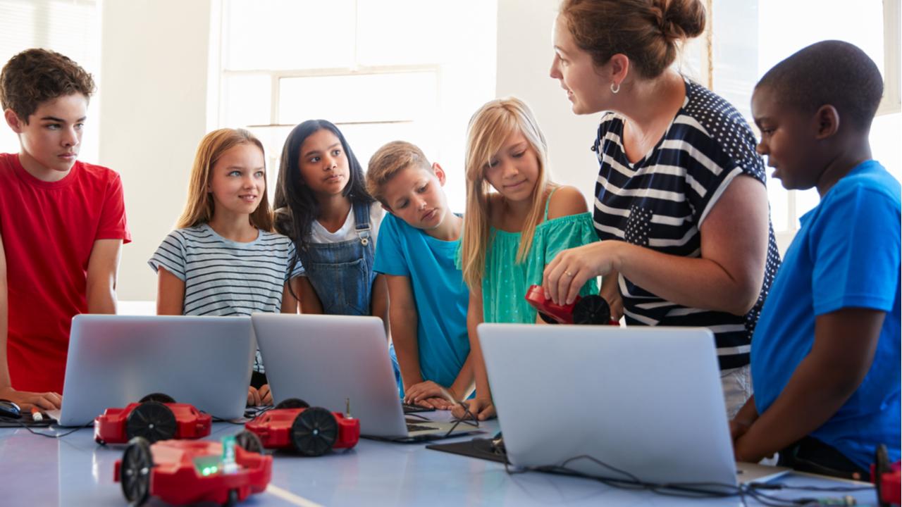 A teacher with a group of kids going over robotics after school.
