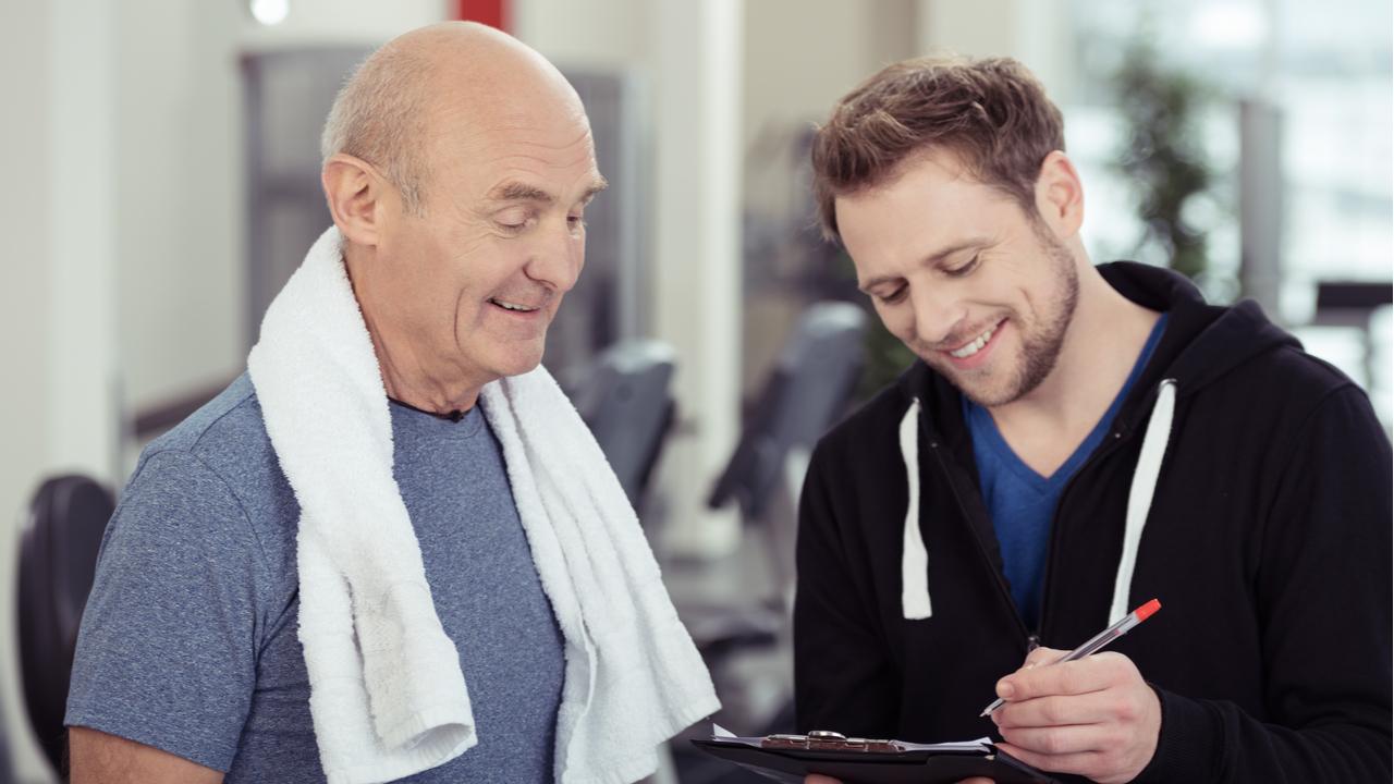 Older man in grey speaking with gym employee.