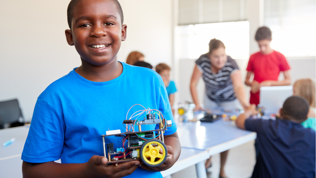 Kid in a blue shirt showing off his robotics project.