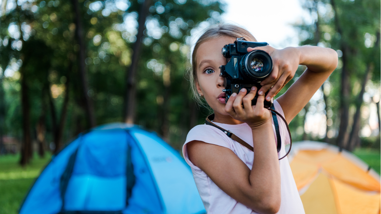 Little girl at camp taking a photo with camera.