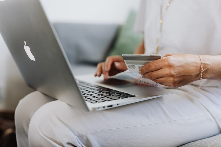 Woman holding a credit card by a computer